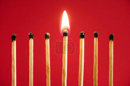Foto de Partido con fuego entre cerillas quemadas sobre fondo rojo - Imagen libre de derechos
