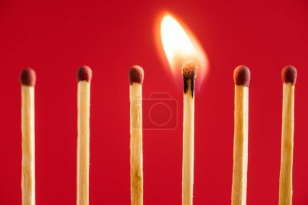 Photo for Match with fire among burned matches on red - Royalty Free Image