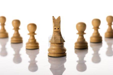 Photo pour Concentration sélective du chevalier avec des pions sur fond blanc - image libre de droit