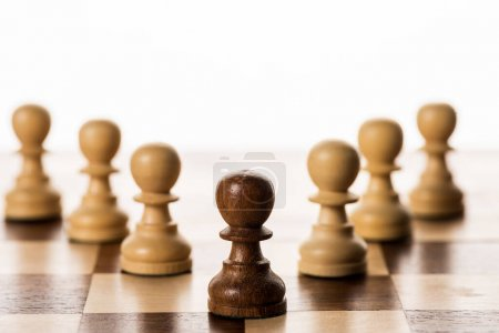Selective focus of brown pawn among another on chessboard isolated on white
