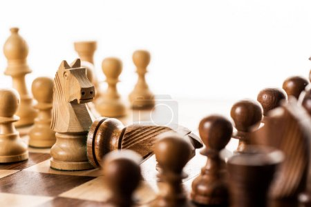 Photo for Selective focus of knights and pawns on chessboard isolated on white - Royalty Free Image