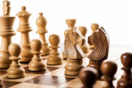 Выборочный фокус шахматных фигур на шахматной доске изолирован на белом