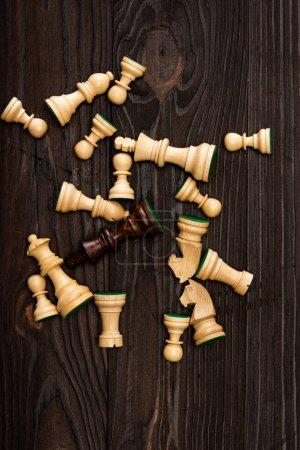 Photo pour Vue du dessus du roi brun unique parmi les pièces d'échecs blanches sur fond en bois - image libre de droit