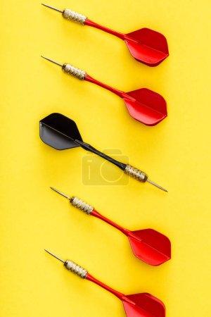 Photo pour Pose plate avec fléchette noire unique parmi le rouge sur le jaune - image libre de droit