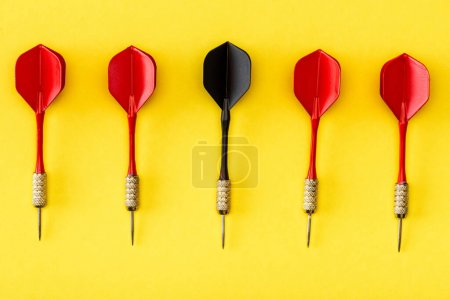 Photo pour Pose plate avec fléchette noire parmi le rouge sur le jaune - image libre de droit