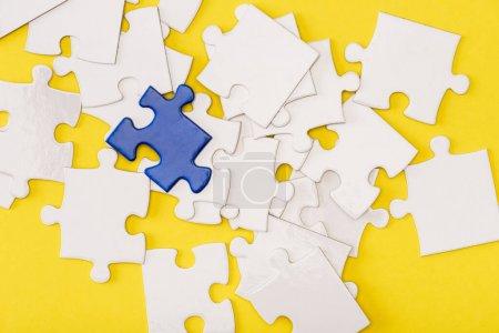 Foto de Vista superior de la pieza azul única del rompecabezas entre blanco y amarillo. - Imagen libre de derechos