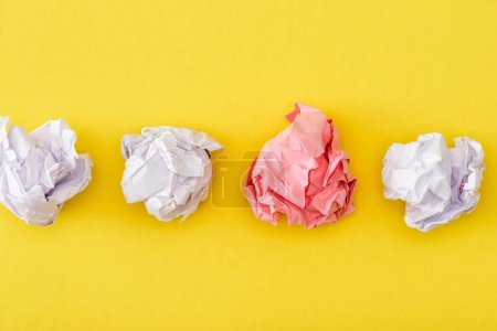 Top view of unique crumpled pink paper among white on yellow background