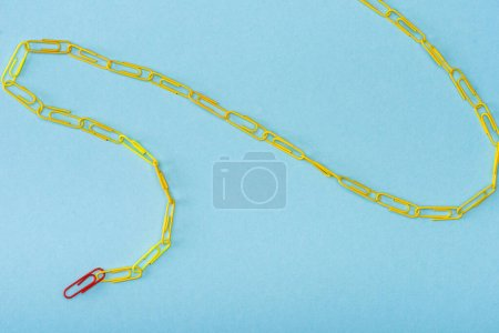 Photo for High angle view of chain with unique red and yellow paper clips on blue - Royalty Free Image