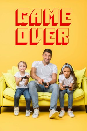 Photo for KYIV, UKRAINE - MARCH 4, 2020: smiling father and children playing video game with joysticks on sofa on yellow, game over illustration - Royalty Free Image
