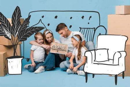 Photo pour Parents positifs et enfants tenant la carte avec la maison doux lettrage à la maison et illustration de meubles tout en étant assis sur bleu avec des boîtes en carton pour la relocalisation - image libre de droit