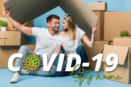 Photo for Happy couple holding carton roof over heads while sitting on blue with cardboard boxes for relocation, covid-19 illustration - Royalty Free Image