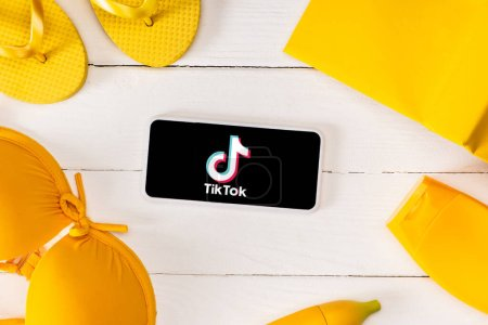 Photo for KYIV, UKRAINE - MARCH 25, 2020: Top view of frame from yellow flip flops with sunscreen, swimsuit and book near smartphone with TikTok app on white wooden planks - Royalty Free Image