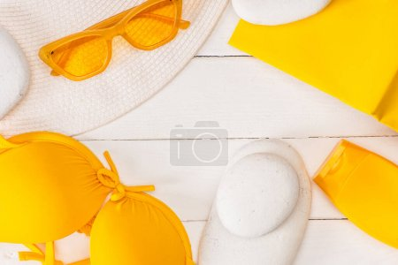 Photo for Top view of sun hat, sunscreen with yellow book and sunglasses on white wooden surface - Royalty Free Image