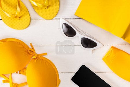 Photo for Top view of sunglasses, yellow swimsuit with sun hat and smartphone on white wooden surface - Royalty Free Image