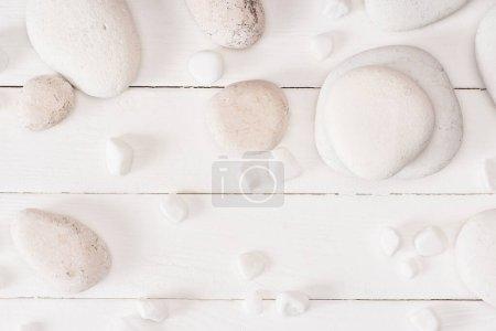 Photo pour Vue en haut des pierres de la mer sur fond blanc en bois - image libre de droit