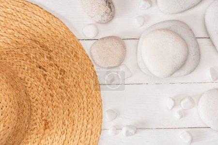 Photo pour Vue du dessus du chapeau de paille avec des pierres de mer sur fond de bois blanc - image libre de droit