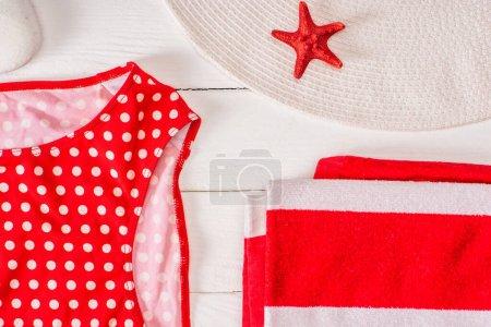 Photo pour Vue de dessus du maillot de bain près de serviette rayée, chapeau de soleil et étoile de mer rouge sur la surface en bois blanc - image libre de droit