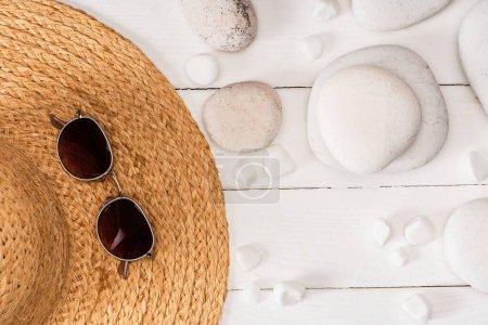 Photo pour Vue du dessus des lunettes de soleil sur chapeau de paille près des pierres de mer sur fond de bois blanc - image libre de droit