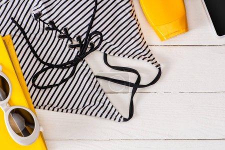 Photo pour Vue du dessus du maillot de bain dépouillé près de la crème solaire, des lunettes de soleil et du smartphone sur une surface en bois blanc - image libre de droit