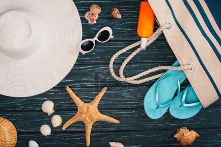 Photo pour Vue du dessus du chapeau de soleil près du sac, des tongs et des coquillages sur une surface en bois sombre - image libre de droit