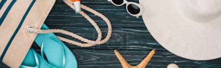 Photo for Panoramic shot of top view of sunglasses, flip flops near bag and starfish on dark wooden surface - Royalty Free Image