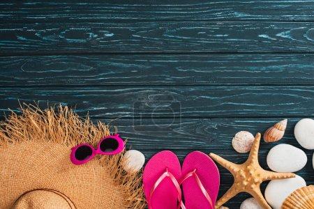 Vista superior del sombrero de paja cerca de gafas de sol rosadas, chanclas y conchas marinas en la superficie de madera oscura