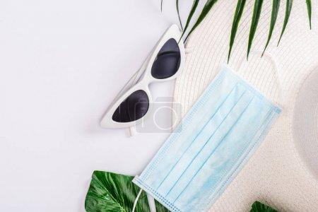 Foto de Vista superior de la máscara médica con sombrero de sol y gafas de sol cerca de hojas verdes en la superficie blanca. - Imagen libre de derechos