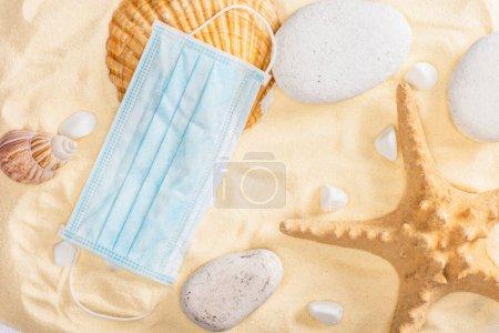 Photo pour Vue du dessus du masque médical près des coquillages et des cailloux sur le sable - image libre de droit