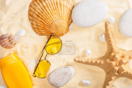 Photo for Top view of sunscreen and sunglasses near starfish and seashells on sand - Royalty Free Image