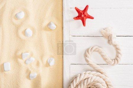 Photo pour Vue de dessus de l'étoile de mer rouge et de la corde sur des planches de bois blanc et des pierres de mer sur du sable - image libre de droit
