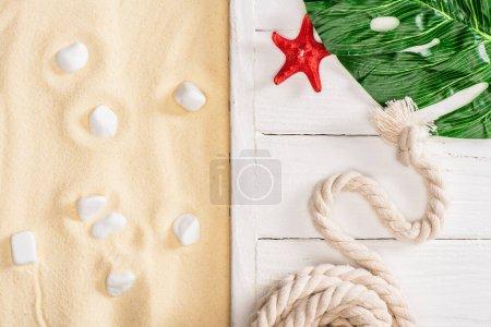 Photo pour Vue de dessus de l'étoile de mer, de la corde et des feuilles vertes sur des planches de bois blanc près de cailloux sur du sable - image libre de droit