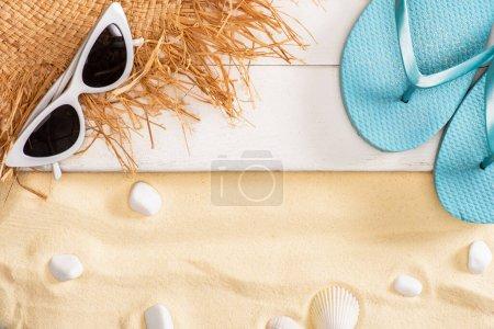 Vue du dessus du chapeau de paille près des lunettes de soleil et des tongs bleues sur des planches de bois blanc et des cailloux sur du sable
