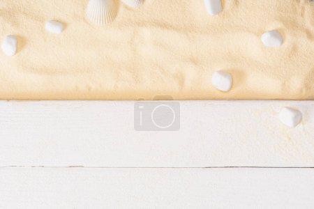 Photo pour Vue du dessus des planches de bois blanc près des pierres de mer sur sable texturé - image libre de droit