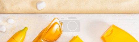 Photo pour Vue panoramique du dessus des lunettes de soleil jaunes près des écrans solaires sur des planches blanches en bois et des cailloux sur le sable - image libre de droit