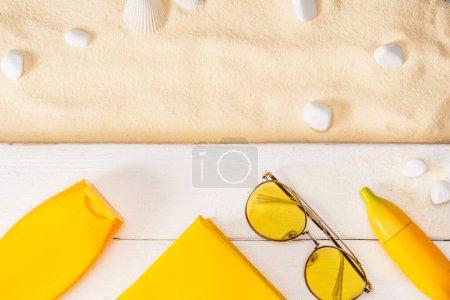 Photo pour Vue de dessus des écrans solaires jaunes, du livre et des lunettes de soleil sur des planches de bois blanc près des pierres marines et des coquillages sur le sable - image libre de droit