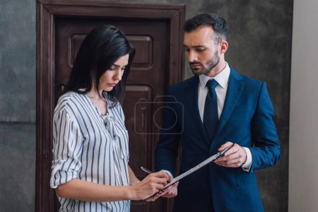 Woman writing in documents in male hands in room