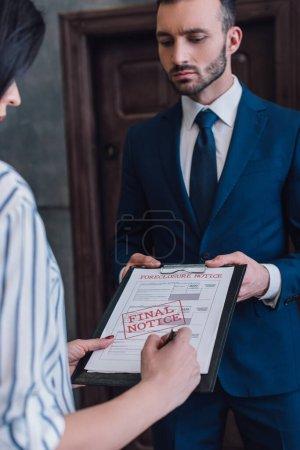 Photo pour Femme écrivant dans des documents avec forclusion et avis final lettrage près de collectionneur dans la chambre - image libre de droit