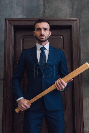 Photo pour Collectionneur en colère avec batte de baseball près de la porte dans la chambre - image libre de droit