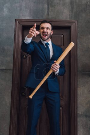 Photo pour Collectionneur en colère avec batte de baseball pointant du doigt et criant près de la porte dans la chambre - image libre de droit