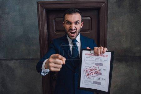 Photo pour Collectionneur en colère avec des documents avec verrouillage lettrage pointant du doigt et criant dans la chambre - image libre de droit