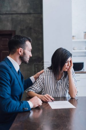 Collector reassuring upset woman with pen and document at table in room