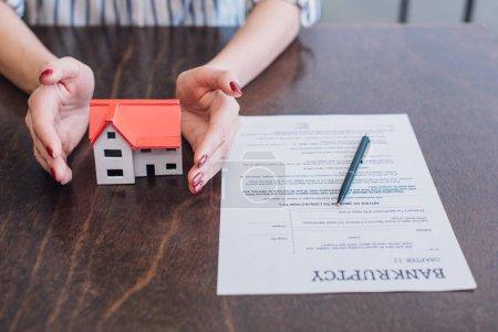 Photo pour Vue partielle des mains de la femme près de la maison Modèle, papier avec lettres de faillite et stylo sur la table - image libre de droit