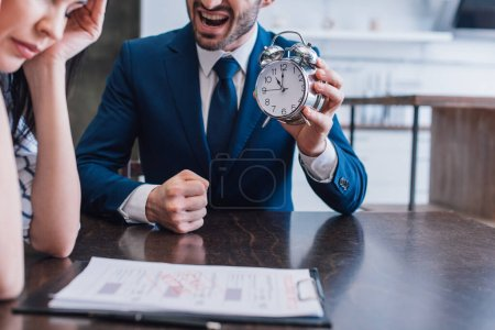 Cropped view of angry collector holding alarm clock near upset woman at table with documents in room