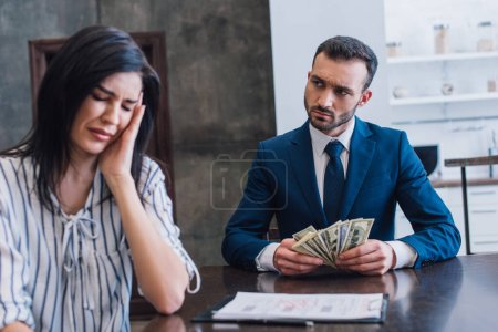 Upset woman crying near collector with dollar banknotes at table in room