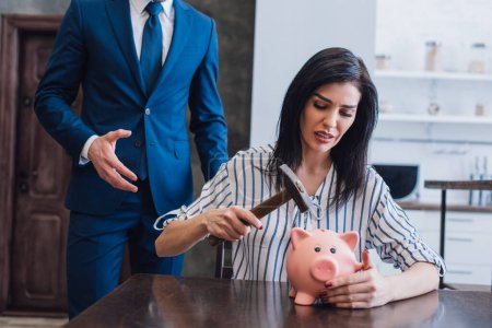 Photo for Worried woman holding hammer above piggy bank at table near collector with outstretched hand in room - Royalty Free Image