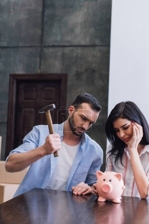 Photo for Woman with tense man holding hammer near piggy bank at table in room - Royalty Free Image