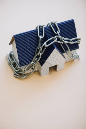 High angle view of house model with chain on white background