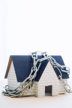 Photo for House model with blue roof and chain isolated on white - Royalty Free Image
