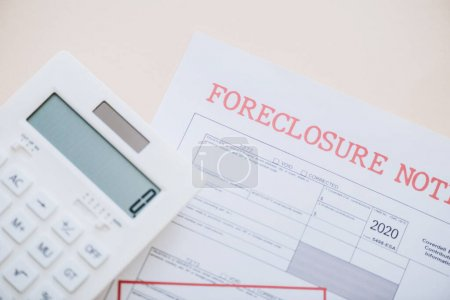 Photo for Top view of document with foreclosure lettering and calculator on white background - Royalty Free Image