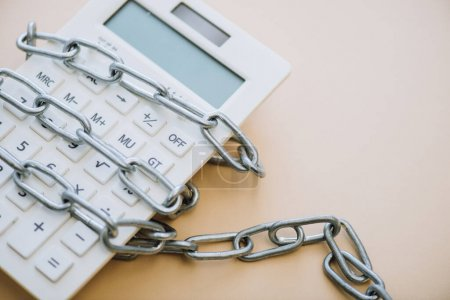 High angle view of calculator with chain on white background